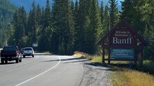Establishing Shot Showing Welcome Sign With Mask Wearing Advisory Due To Covid-19 Pandemic At The Entrance Of Banff Town In Alberta, Canada.