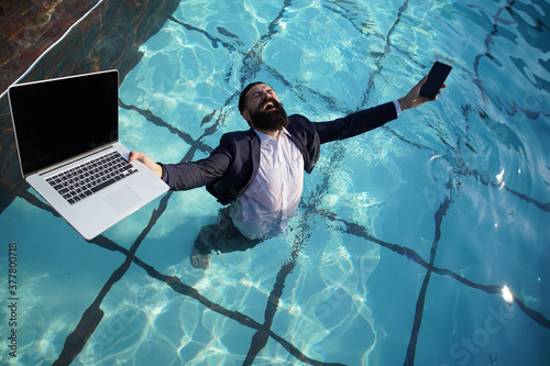 Crazy comic business. Excited business man in suit with laptop and mobile phone on swimming pool. Funny businessman relaxing with laptop.
