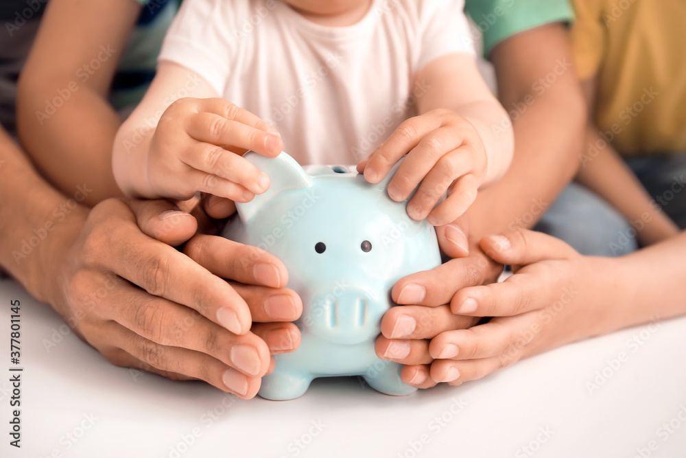 Fototapeta Family with piggy bank at table