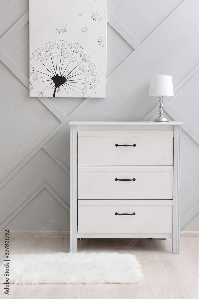 Fototapeta Modern chest of drawers with lamp near grey wall in room