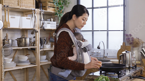 Fototapeta asian female parent carefully holding young child with carrier is preparing brea