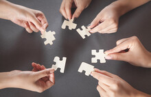 Hands Of People Holding Jigsaw...