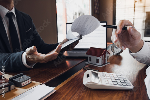 Photo Business people home sales broker is using a pen pointing to the house model and describing the various components of the house