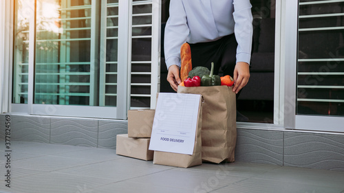 Obraz na plátně Asian woman open the door and took the bag of food ordered by the carrier to put in front of the house to prevent the epidemic