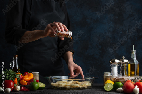 Stampa su Tela Chef grinding mixed red pepper in a pot with dish isolated on dark background