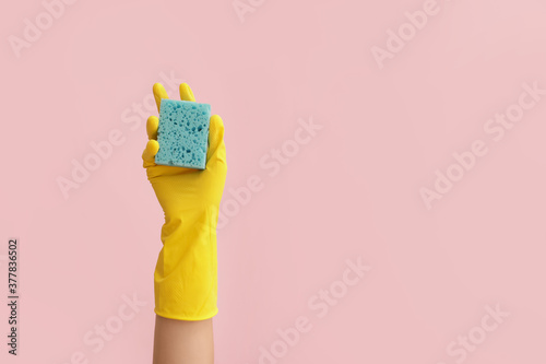 Hand in rubber glove and with sponge on color background Canvas Print