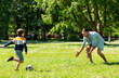 canvas print picture - family, fatherhood and people concept - happy father and little son with ball playing soccer at summer park