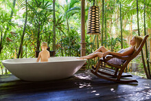 Happy Baby Boy Have Fun In Bathtub, Young Mother Relax On Rocking Chair In Outside Bathroom On Veranda With Beautiful Tropical Garden View At Luxury Villa On Summer Family Vacation.