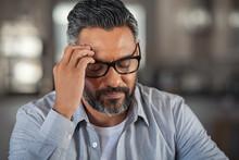 Stressed Ethnic Man With Heada...