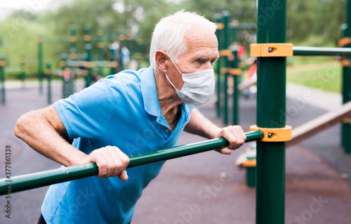 Foto old cheerful pensioner man in medical mask protecting from virus doing physical