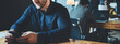 Business office concept. Portrait of handsome manager working at the table with mobile phone. Three employees at background. Wide screen, panoramic