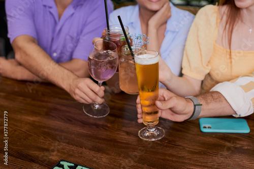 Obraz na plátně close-up photo of hands clinking glasses wit beer, alcoholic coctails