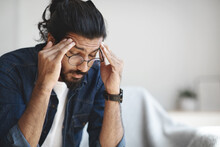 Young Indian Guy Freelancer Suffering From Headache After Hard Working Day