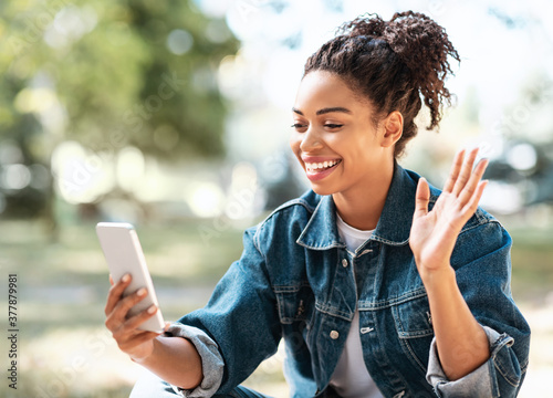 Fototapeta Black Woman With Cellphone Making Video Call Waving Hello Outside obraz