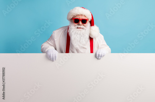 Portrait of his he nice attractive funky cheery confident white-haired Santa holding in hands demonstrating copy space board advert ad isolated over bright vivid shine vibrant blue color background