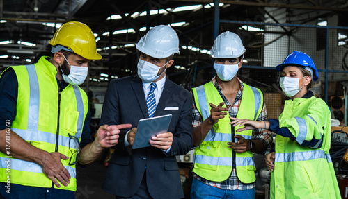 Fototapeta Industrial engineers and businessman in suite and safety helmet wearing mask working in factory, planning, discussing and training workers with tablet in metalwork place , teamwork and team concept obraz
