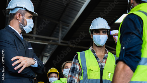 Fotografie, Obraz Industrial worker and engineer stand in line to check flu with infrared thermome