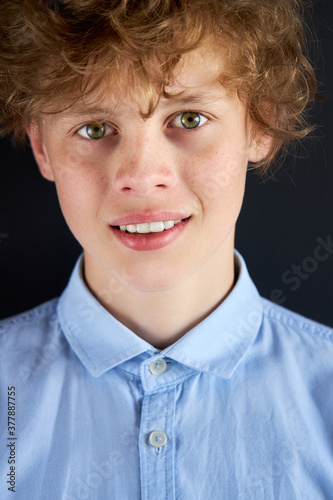 portrait of calm caucasian boy looking at camera, male teenager in blue shirt isolated over black background