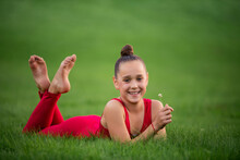 Girl Schoolgirl Gymnast In Bright Red Overalls Is Resting On Grass In The Park, Holding A Clover Flower In Her Hands, Laughing. She Has Braces On Her Teeth.