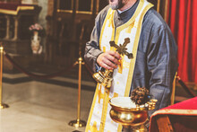 Orthodox Priest Holds A Golden Cross In An Orthodox Church During A Religious Ceremony