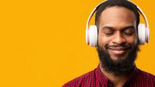 Smiling Black Man Enjoying Music Using Headphones