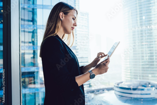 Fototapeta Confident professional female lawyer using app on touchpad connected to wireless internet making research in office,blonde business woman in formal wear browse via digital tablet near panoramic window obraz