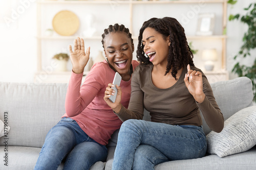 Fototapeta Two cheerful young female friends singing at home