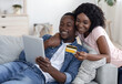 Leinwandbild Motiv Happy married couple with digital tablet buying furniture online