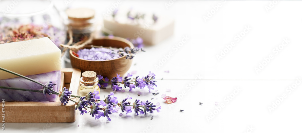 Fototapeta Lavender's soap bars and Spa products with lavender flowers on a white table.