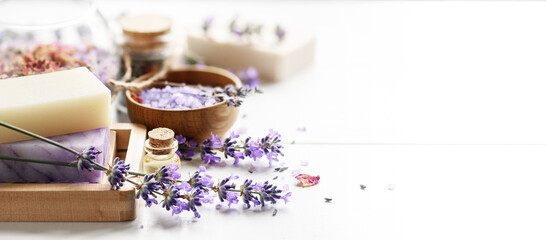 Lavender's soap bars and Spa products with lavender flowers on a white table.