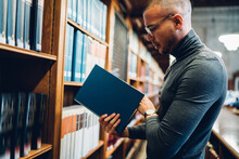 Caucasian Male Student Choosing Book For Reading Standing Near Shelves In Old Public Library, Side View Of Academic Professor Spending Time In Archive Selecting Literature For Increasing Knowledge