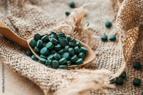 Foto Wooden spoon with spirulina tablets against the background of burlap