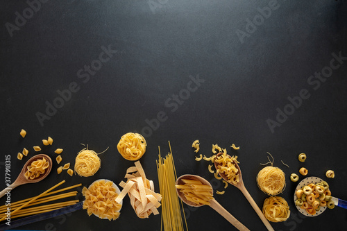 Fotografia Pasta assortment on black background, top view