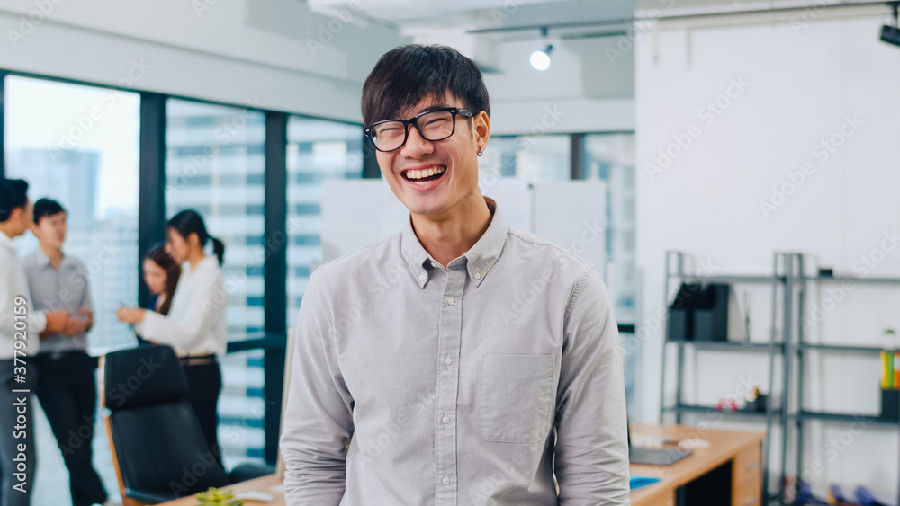 Fototapeta Portrait of successful handsome executive businessman smart casual wear looking at camera and smiling, happy in modern office workplace. Young Asia guy standing relax in contemporary meeting room.