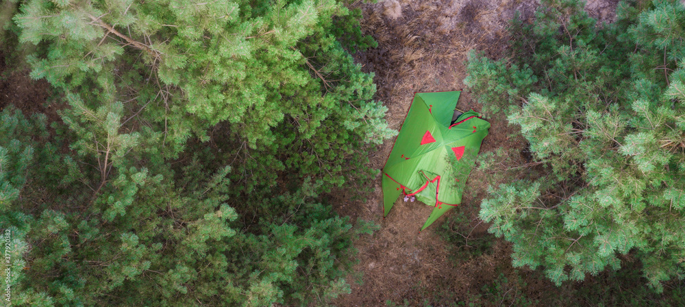 Fototapeta Aerial tent in the forest. Camping background concept. Active lifestyle