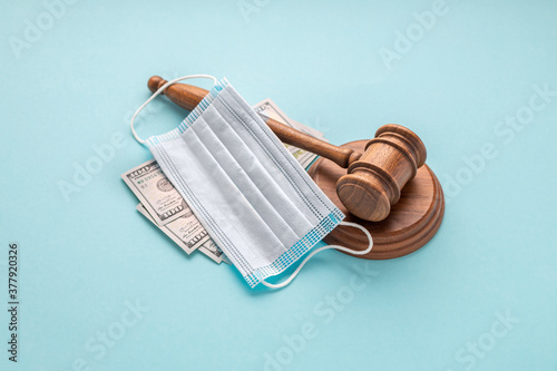 Fototapeta Corruption in the medical field concept. Judge gavel with medical mask and money on blue background obraz