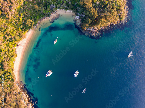 Photo Aerial drone bird's eye view of sailboats and yachts anchored at Store Beach near Quarantine Station in Manly, the beachside suburb of Sydney, New South Wales, Australia, in the evening before sunset