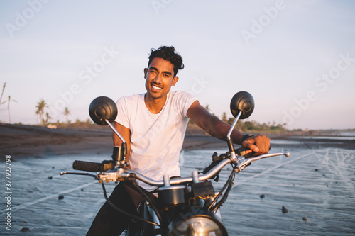 Fotografie, Obraz Cheerful young ethnic man smiling on motorbike on seaside