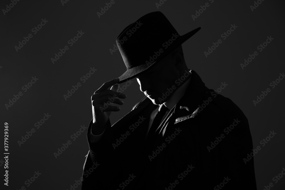 Fototapeta Old fashioned detective in hat on dark background, black and white effect