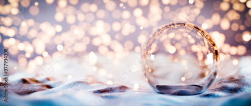 Obraz Christmas glass ball on snow. Glitter lights - fototapety do salonu