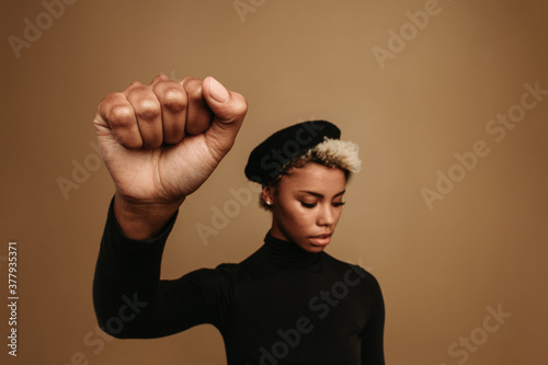 African american woman with raised fist on brown background Fototapeta