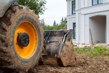 Bulldozer Is Being Prepared To Demolish An Illegally Built Private House In Natural Area. Close - Up Photo Of Tractor Bucket In Front Of Cottage Entrance