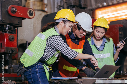 Asian male engineer or foreman worker training female trainee using program or system in industry manufacturing factory Fototapet