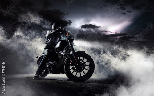 Foto Detail of high power motorcycle chopper with man rider at night.