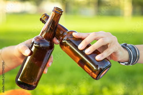Fototapeta The hands holding bottles with beer and making cheers obraz