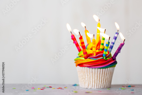 Fotografia Birthday cupcake with rainbow frosting and candles