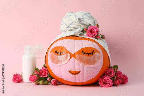 Leinwand Poster Skincare supplies, pumpkin with eye patches and towel on pink background