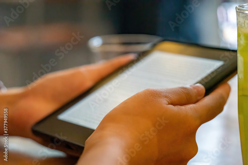 Fototapeta hands of a girl holding a e-book device over a wooden table in coffee shop, selective focus. obraz na płótnie