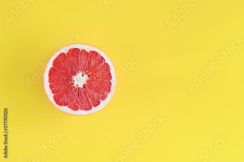Obraz na plátně Juicy ripe slice, piece, half of red pink grapefruit is on left side of yellow background canvas