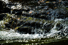Close Up Of Clean Clear Water Rushing Over Rocks In A River Stream.